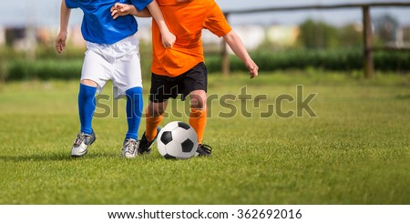 young boys playing football soccer game. Running players in blue and orange uniforms