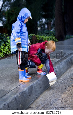 Young boys playing with toy boat in the rain wearing rain slickers and galoshes.