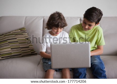 Young boys using laptop while sitting in the living room at home