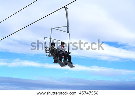 Young Boys with snowboards riding chair lift - stock photo