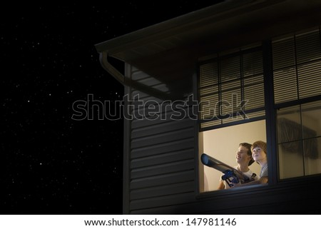 Young boys with telescope at open window looking at night sky - stock photo