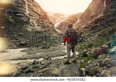 Young brave man with a backpack standing in front of a glacier