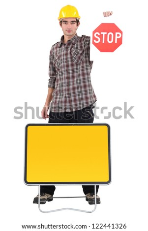 Young bricklayer holding stop sign - stock photo