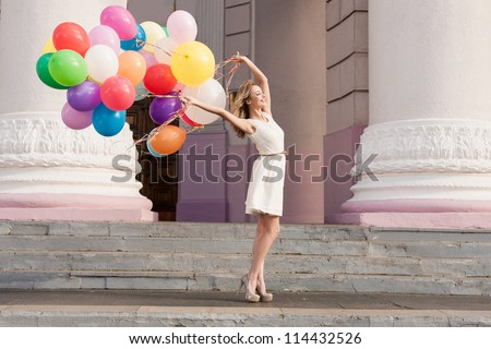 Young bridal with colorful latex balloons keeping her dress, urban scene, outdoors - stock photo