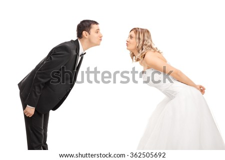Young bride and groom standing opposite of each other and going in for a kiss isolated on white background - stock photo