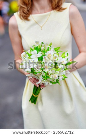 Young bride holding in her hands beautiful wedding flowers