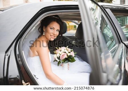 Young bride in a wedding car. Bridal bouquet. - stock photo