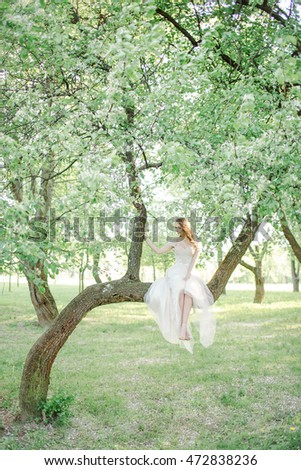 Young bride in beautiful wedding dress sitting on tree outdoors in park