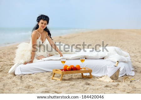 Young bride in bed at the coastline against cloudy sky - stock photo