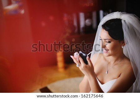 Young bride is getting ready at home, having make up, using phone like a  mirror. - stock photo