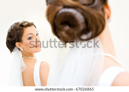 young bride looks at herself in the mirror