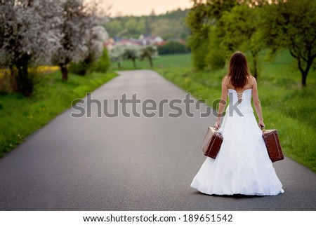 Young bride on the road with a suitcase - stock photo