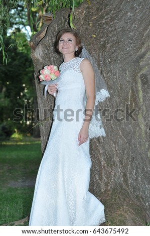 Young bride posing for the camera outdoor in the park