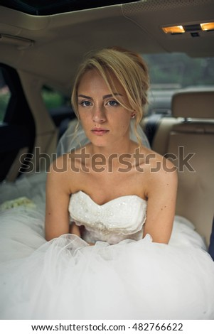 young bride sits in the big car