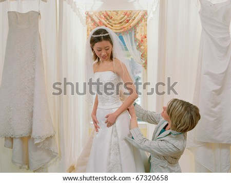 Young bride-to-be trying on her gown with the help of an employee
