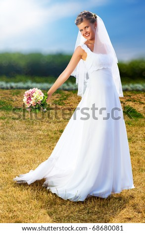 Young bride walking in park. - stock photo