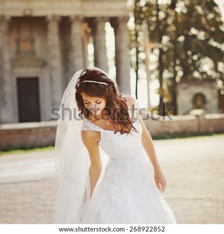 Young bride wearing wedding dress and posing outside against an old church.  - stock photo