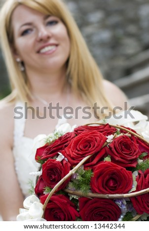 young bride with bouquet of red roses - stock photo