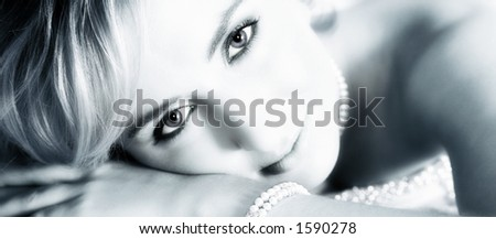 Young bride with large eyes resting on her hands - strong eye-contact - stock photo