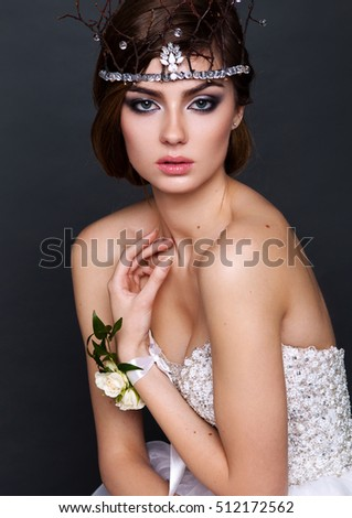 Young bride woman in wedding dress on grey background in the studio with make up and hairstyle