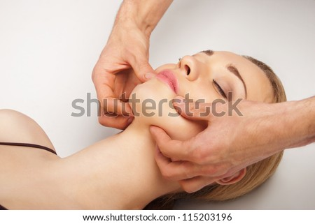 Young bright woman receiving a head massage in a spa center - stock photo
