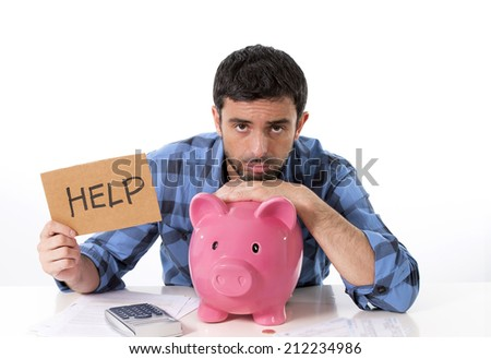 young broke man in stress feeling sad leaning on empty piggy bank with calculator accounting bad financial situation asking for help in billboard sign wearing casual shirt isolated on white background - stock photo