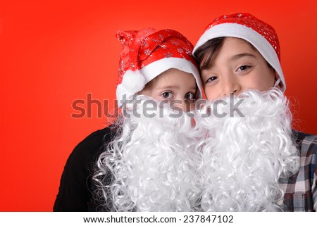 Young brothers funny portrait with xmas hat and beard against red background.  - stock photo