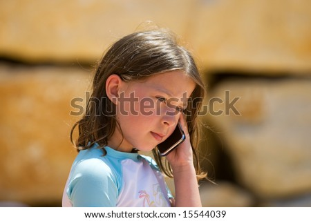 Young Brown Haired Child using Mobile Phone - stock photo