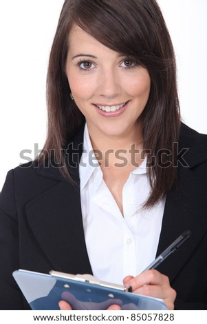 Young brown-haired woman taking notes - stock photo