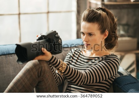 Young brunet woman is sitting on couch and holding dslr photo camera - stock photo