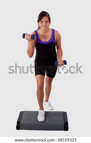 Young brunette aboriginal teen girl wearing workout attire using aerobic stepper while holding hand weights over white background - stock photo