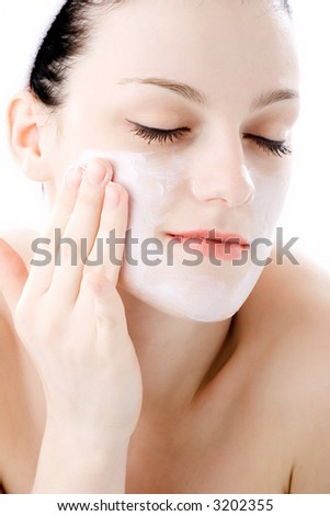 young brunette applying creme on face - stock photo