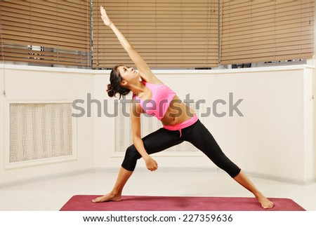 Young brunette arm and leg in straight line yoga pose looking at palm