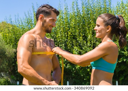 Young brunette athlete in sportswear, measures the chest of muscular shirtless man at the park. Healthy lifestyle and fitness concept. - stock photo