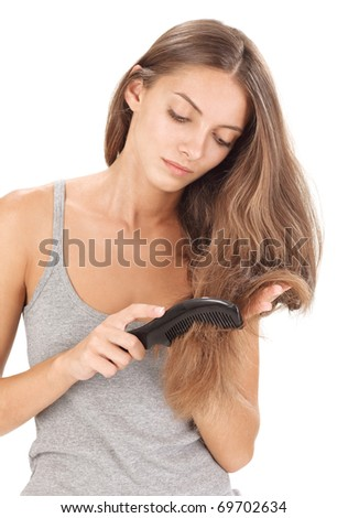 Young brunette beautiful lady combing long hairs on white