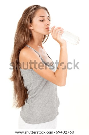 Young brunette beautiful lady drinking gas water in bottle on white