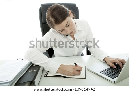 young brunette business woman busy with telephone and laptop