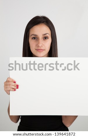 Young brunette caucasian woman holding a blank sign