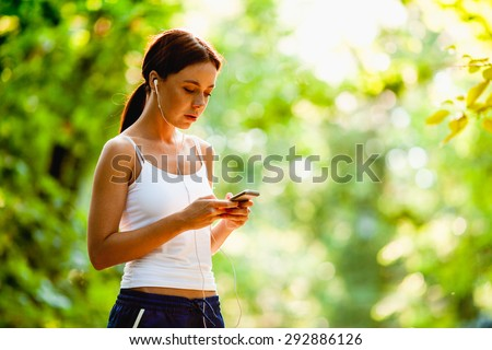 Young brunette caucasian woman with mp3 player doing fitness in city park - stock photo