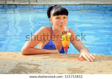 Young brunette drinking cocktail in the pool - stock photo