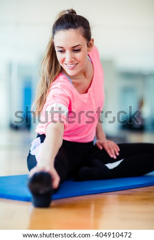 Young brunette european white caucasian girl exercising alone in gym with wooden floor doing yoga, pilates and fitness exercises - stock photo