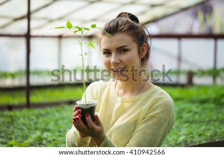 Young brunette farmer girl taking care of green seedling plants in greenhouse with a happy smile. She is satisfied of how her vegetable sprouts grow under the sun in this hothouse.  - stock photo