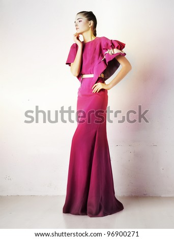 Young brunette fashionable woman in fashion red long dress posing isolated in studio - stock photo