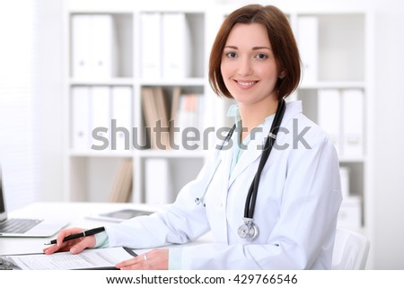 Young brunette female doctor sitting at the table and working at hospital office.  Health care, insurance and help concept. Physician ready to examine patient - stock photo