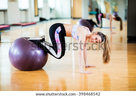 Young brunette female student in her 20s exercising at studio / gym with black long pants and sports top - stock photo