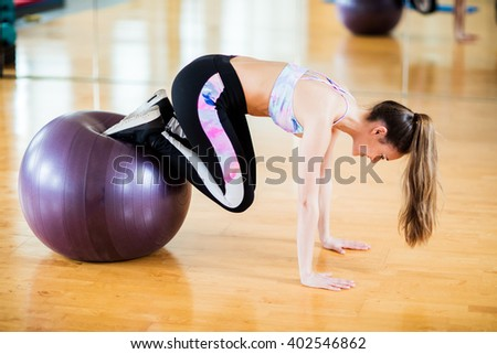 Young brunette female student in her 20s exercising at studio / gym with black long pants and sports top