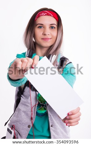 Young brunette female student standing and listening to music from your device. Beautiful young backpacker. Young female student holding a white sheet - stock photo