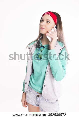 Young brunette female student standing and looking at her smartphone. Beautiful young backpacker - stock photo