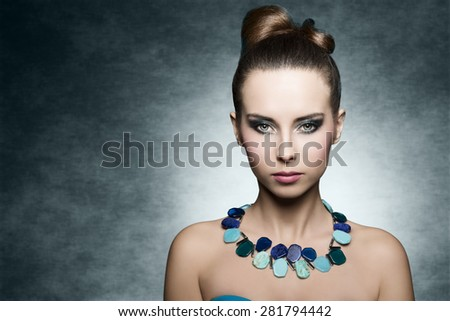 young brunette female with charming expression pose in beauty close-up portrait with stylish turquoise make-up and fashion summer necklace. Creative hair-style  - stock photo
