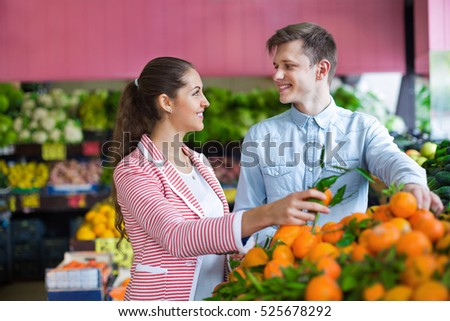 Young brunette girl and boyfriend buying citruses in grocery store